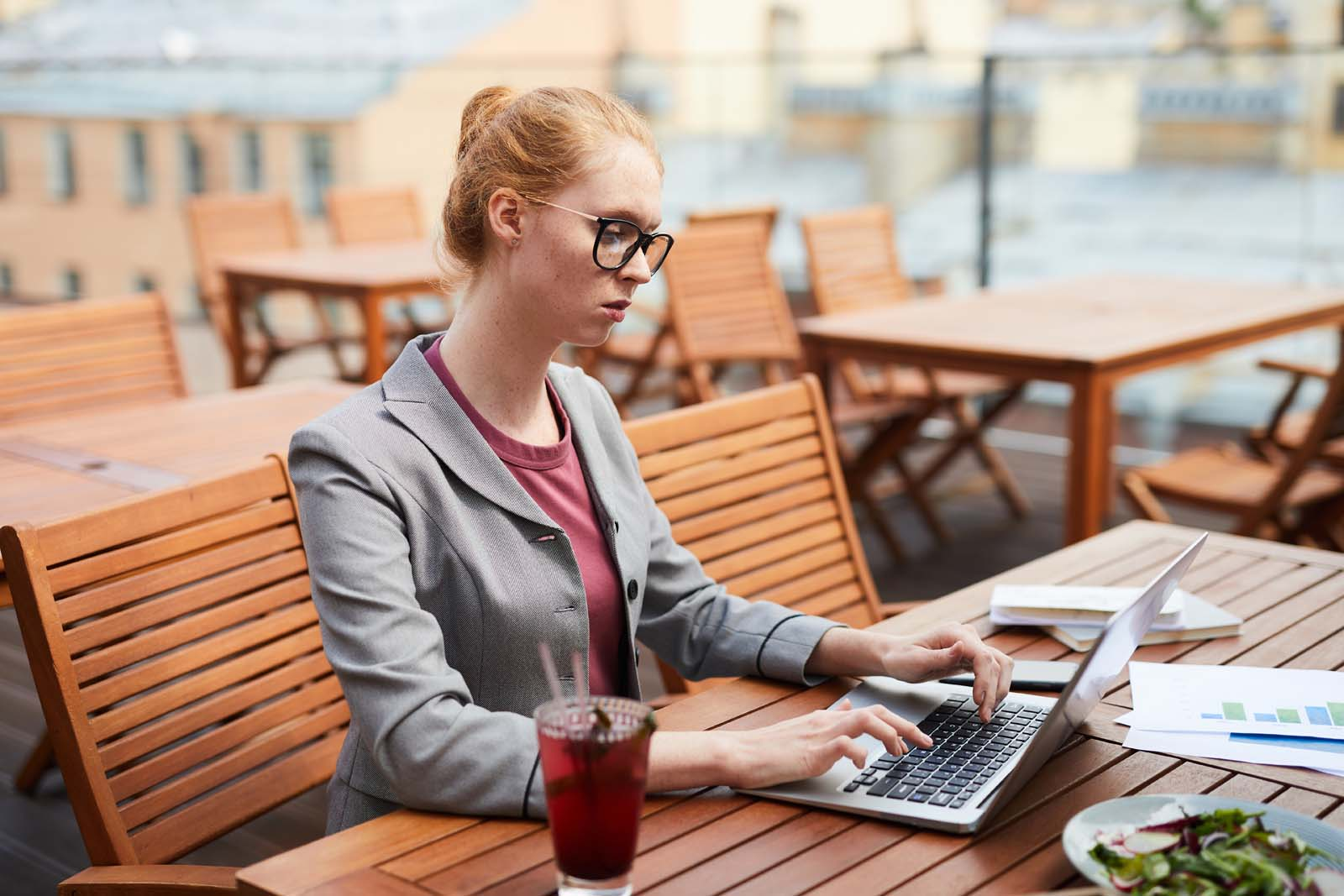 professional looking freelance woman working at coffee shop