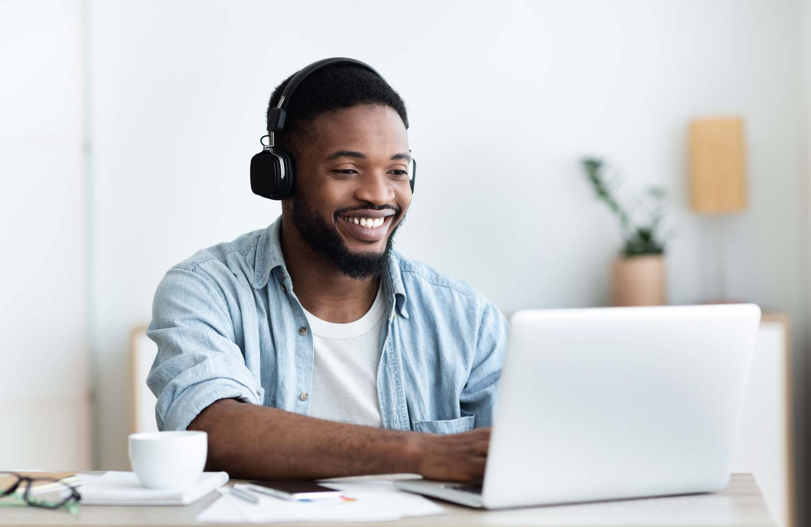 smiling freelance working with headphones and laptop
